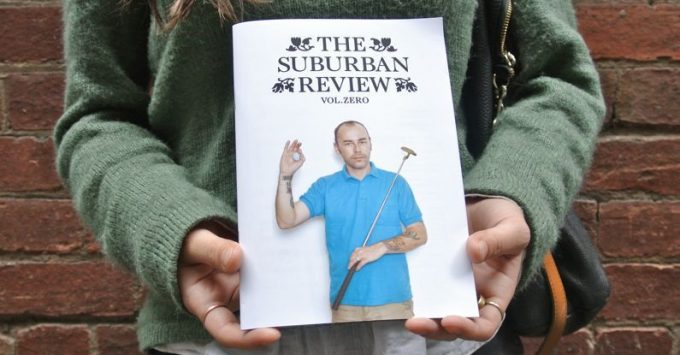 Vol. 0 of The Suburban Review is gently held in the hands of someone wearing a green jumper. Their face is not visible.