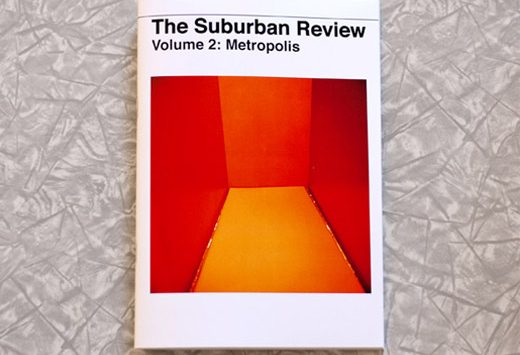 The cover of Vol. 2: METROPOLIS of The Suburban Review sits flat on a tabletop covered in a lace tablecloth. The cover shows a room, 3 walls and the wall are visible. Each wall is awash with a different shade of red or orange.