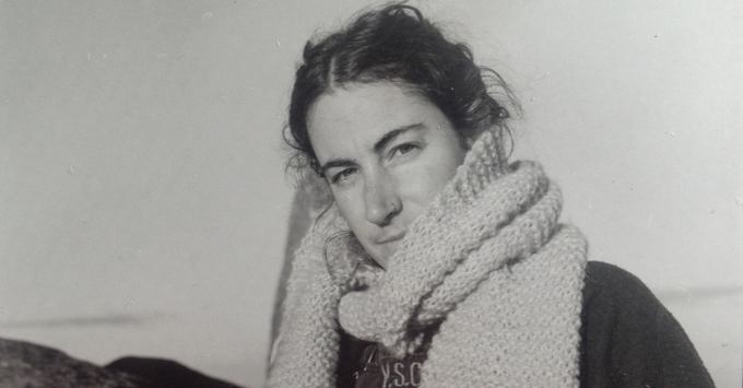 A black and white image of a person with a massive knitted scarf around their neck. The image shows their head and shoulders, with a mostly white backdrop, with the vague outline of a small rocky outcrop behind them.They have long, dark hair that is pulled back, but some wispy curls are present around their face. They wear a dark shirt, and they are smiling slightly.