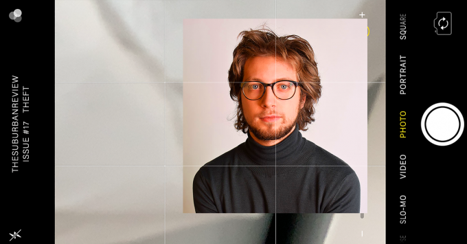 "A photograph of illustrator Eric Kons in a black turtleneck and round black glasses sits superimposed on a background featuring a phone screen in landscape orientation. The phone screen is set to a camera app which is displaying an undulating gray background, and the top of the screen reads ""THE SUBURBAN REVIEW ISSUE #17 THEFT."""