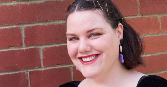 A photograph of artist Clea Chiller against a brick wall background. Clea is smiling broadly at the camera. She has a dark brown bob. Her hair is pushed back with three bobby pins. She is wearing dangly geometric pink and purple earrings.