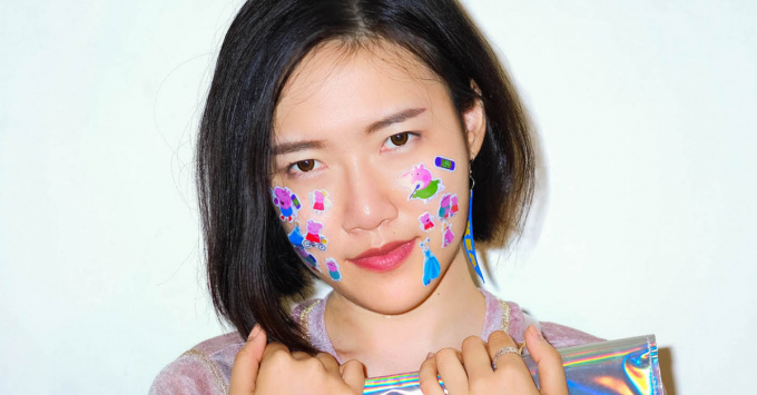 A photograph of artist Amy Yang against a white background. Amy Yang is holding folded silver holographic material against her chest. She has a chin-length black bob and is looking directly into the camera. Her hair is tucked behind her ear on the left side. A blue and yellow piece of fabric with IKEA on it dangles from her ear. Colourful Peppa Pig and Disney Princess stickers dot her cheeks.
