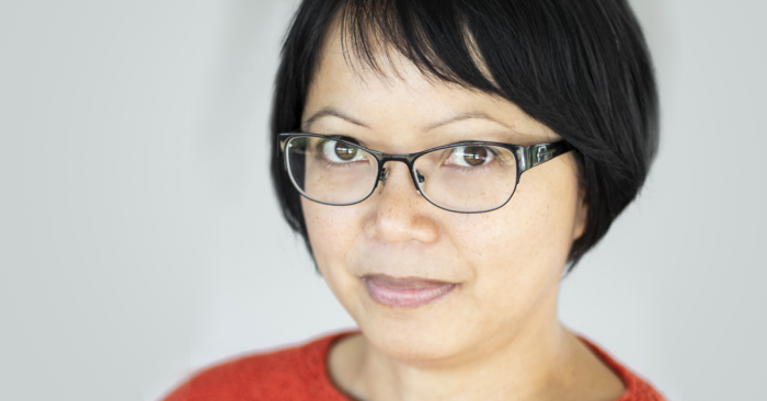 A photograph of writer Ivy Alvarez against a pale grey background. She has short black hair with a side fringe. Ivy is wearing glasses with black frames and a red top. She is looking up at the camera with a slight smile.