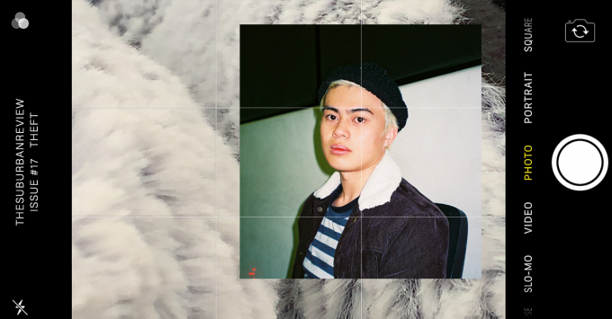 A photograph of artist Tim Sta-Ana. Tim has pale blonde hair tucked into a black beanie. He is wearing a blue and white striped top underneath a black denim shearling jacket. He is turned towards the camera with a slight smile. This photo is superimposed on a background featuring a phone screen in landscape orientation. The phone screen is set to a camera app which is displaying a grey fuzzy texture on a black background. The top of the screen reads 'THE SUBURBAN REVIEW ISSUE #17 THEFT.'