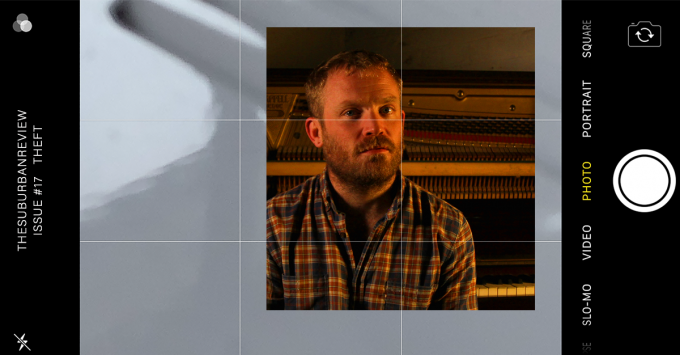 An image of writer Dave Drayton. There is a square photograph of Dave from his chest up. He has short dark blonde hair and blue eyes. Dave is dressed in a slightly open red and blue flannel shirt. His face is turned slightly towards the camera with a serious look. The photo is bathed in warm sepia tones and you can see a piano in the background. This square photo is superimposed on a background featuring a phone screen in landscape orientation. The phone screen is set to a camera app displaying a white background with a shadow falling across it. The top of the screen reads 'THE SUBURBAN REVIEW ISSUE #17 THEFT.'