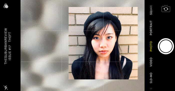A head and shoulders image of Joanna Du. Joanna has long, straight black hair, a black beret, black winged eyeliner and a black long sleeved shirt. She is standing against a light coloured brick wall. The image is overlaid over an indistinct, beige background. The image is viewed on the camera of a smartphone.