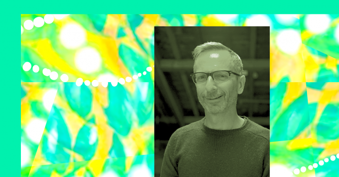 Seafoam green bordered the abstract pattern. Aqua leaves splashed across a golden background, lines of white dots flow across the pattern in different directions. Tony is standind under exposed wooden beams. Wearing a t-shirt and glasses, Tony is smiling at the camera.